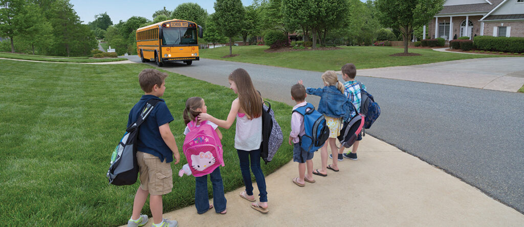 Kids standing on sidewalk with green grass in front and black pavement to the right. A yellow school buses approaches on the pavement