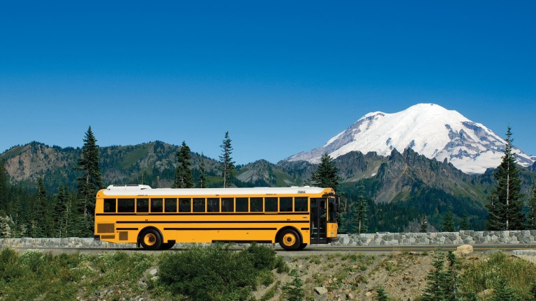 Yellow school bus on a road with blue skies, green trees, and a white mountain in the background covered in snow