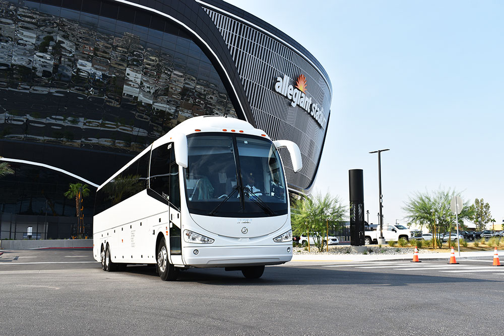 White charter bus with large black building in the background with blue skies.