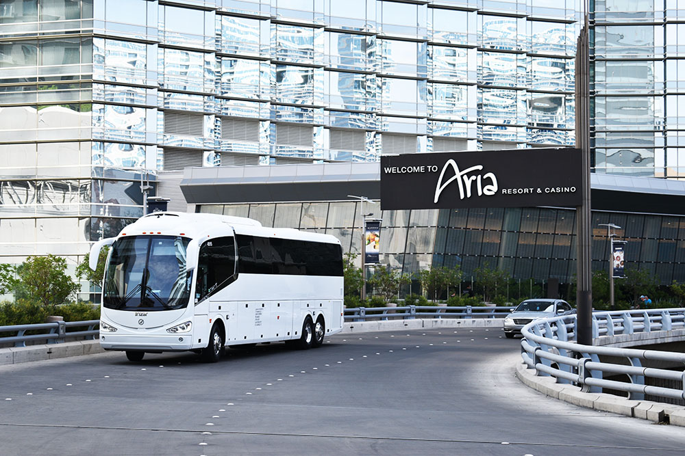 White charter bus driving on black pavement with large glass building in background.