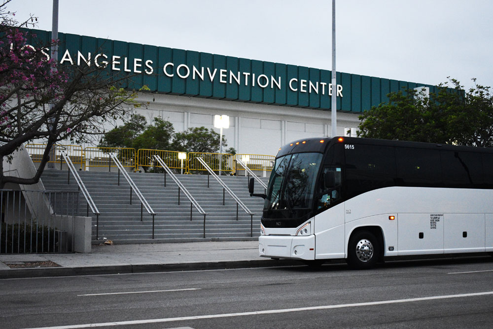 White charter bus parked in front of Los Angeles Convention Center