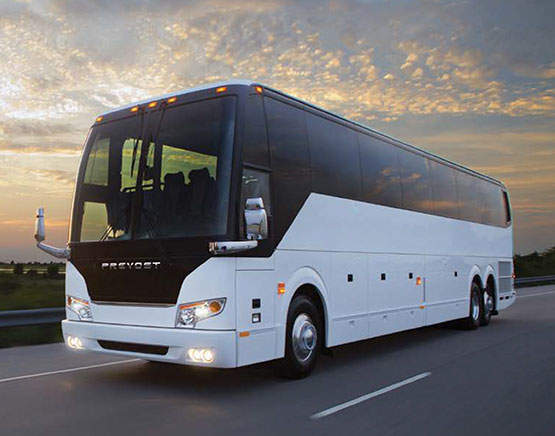 White tour bus rental with blue skies and Los Angeles sunset in the background