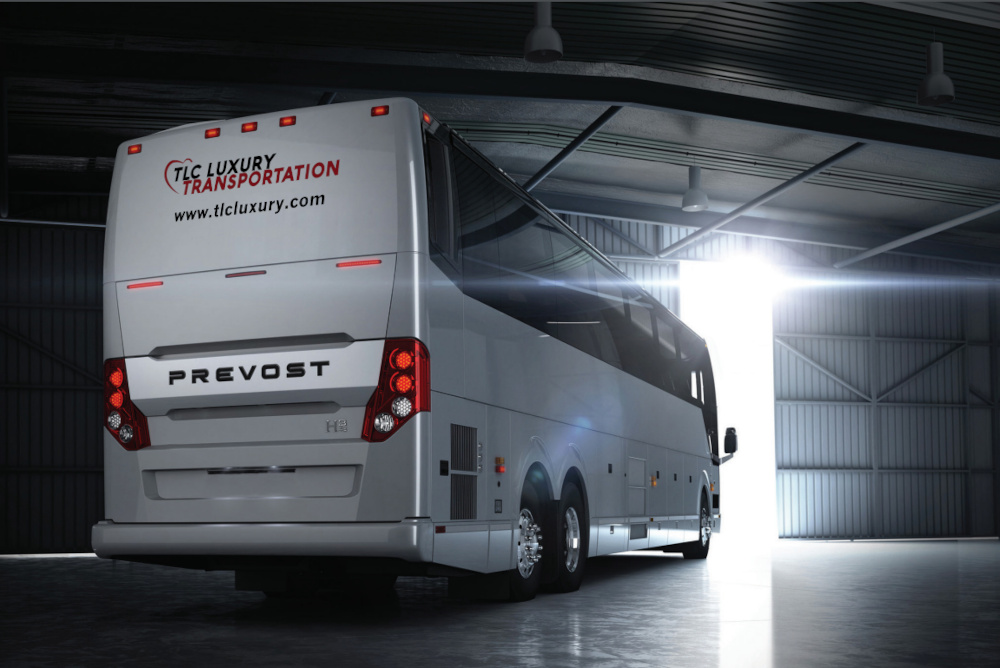 White tour bus rental with TLC Luxury logo on the back of the vehicle with the front end facing the opening doors of a warehouse with sunlight shining through