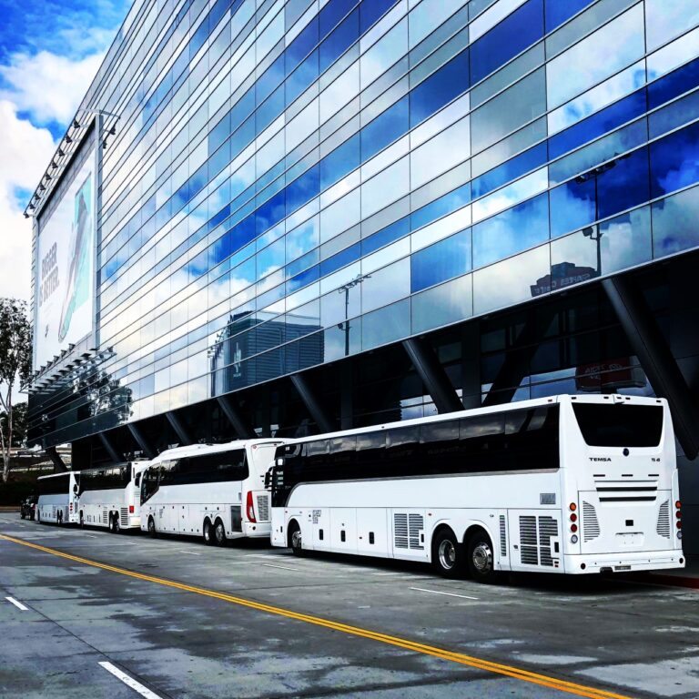 Blue and white patterned building with clouds in reflection and white los angeles charter buses below parked on the street