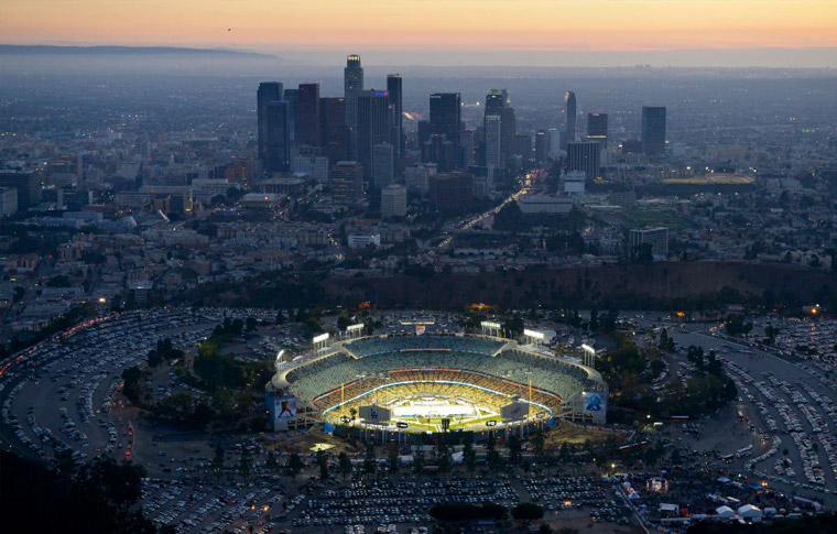 Aerial view of Dodgers Stadium lit up at sunset with Downtown Los Angeles in the back ground.