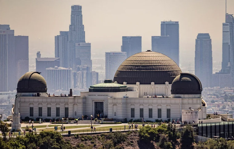 White building with a round roof overlooking buildings in the background during a hazy day