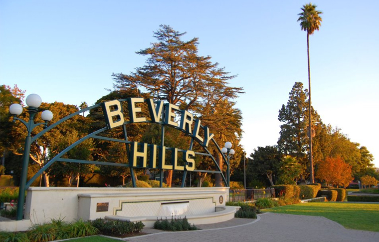 Blue skys, large trees, and sign reading Beverly Hills