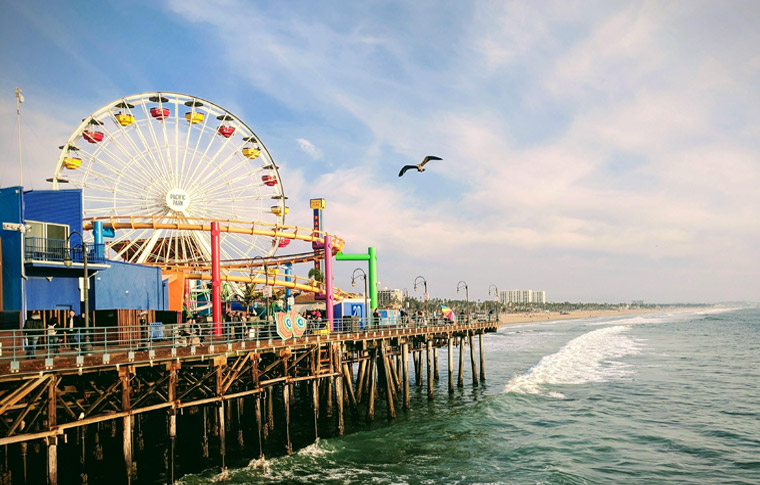 blue skies above a colorful pier with amusement rides overlooking the ocean with a wave forming as a bird flies overhead