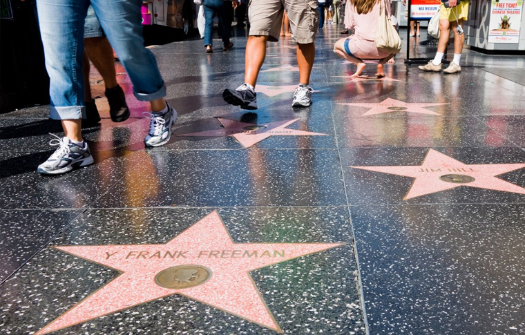 Feet of people walking on black colored sidewalk with stars containing the names of Hollywood celebrities