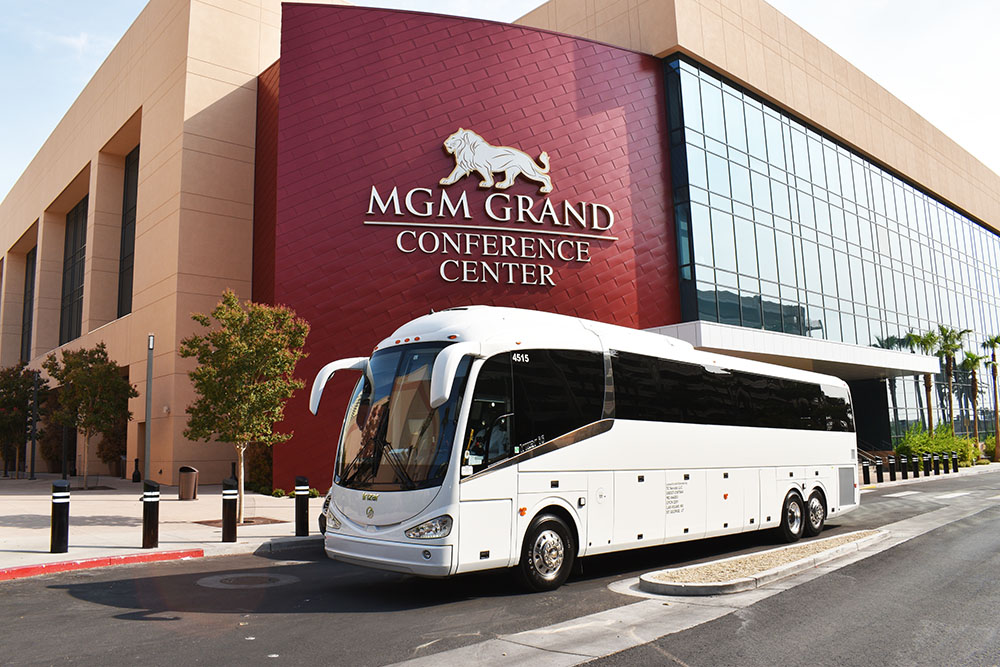 White charter bus underneath red building with sign reading 'MGM Conference Center'